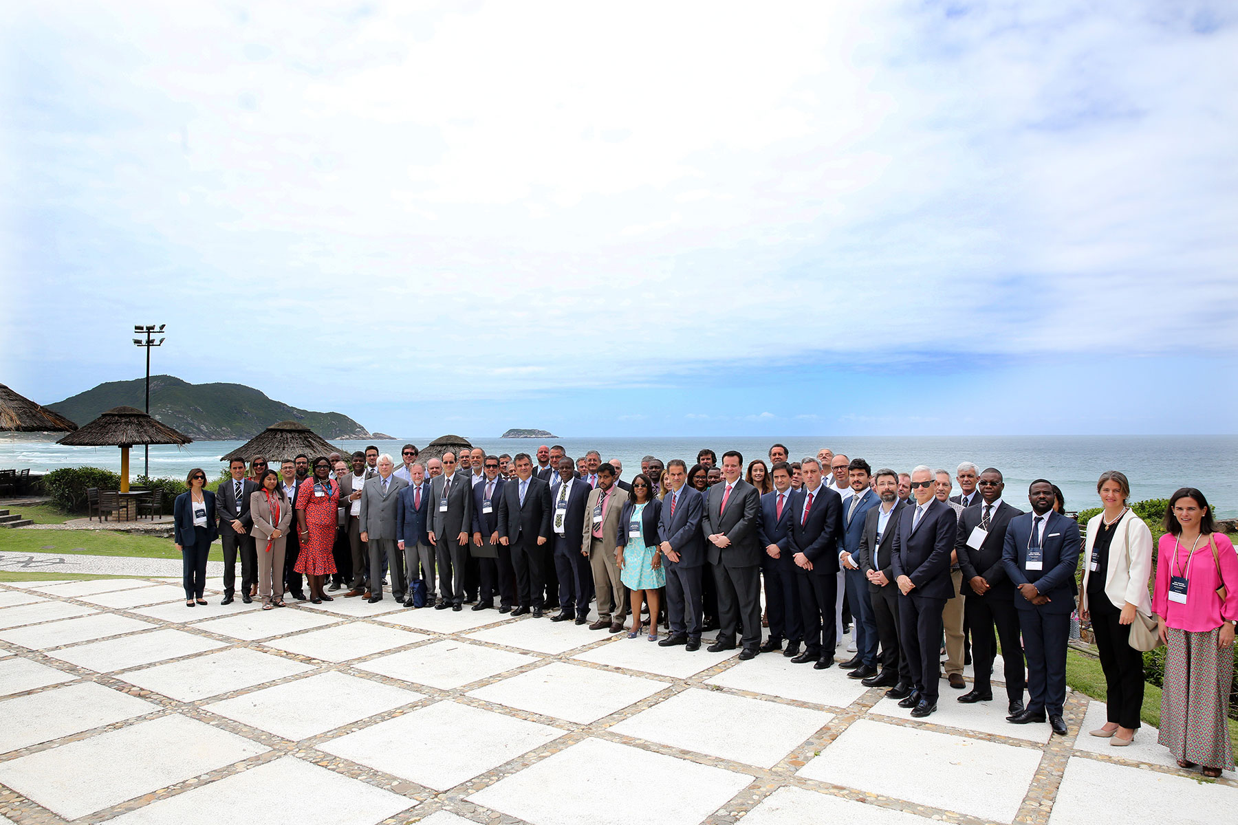 Group of attendees from the Second High-Level Industry-Science-Government Dialogue on Atlantic Interactions stand on the beach in Florianopolis, Brazil