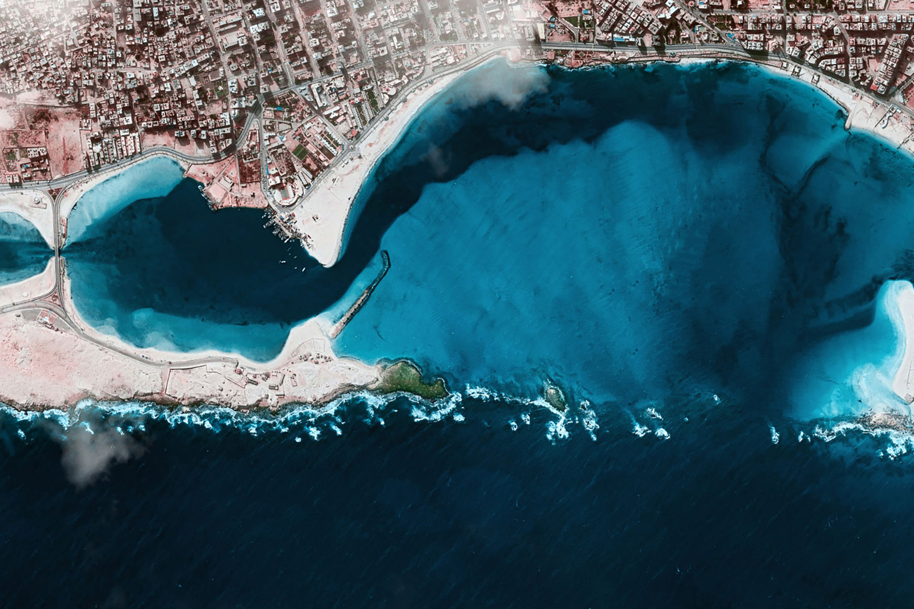 Aerial satellite photograph of an inlet next to a coastal city.